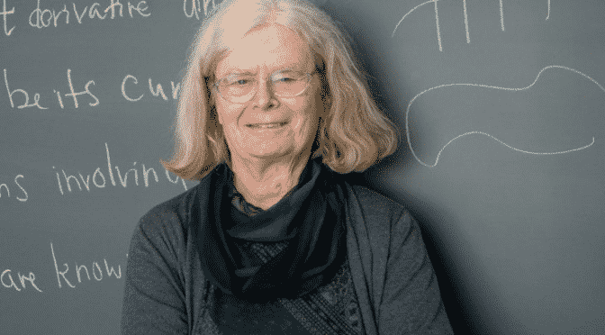 Karen Uhlenbeck stands in front of chalkboard filled with mathe equatons with her arms folded wearing a green sweater