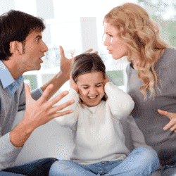 Co-parenting couple arguing in front of their child