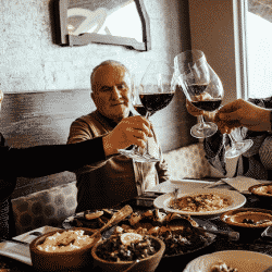 Shawna Stanley is seated at dinner table toasting wine with family