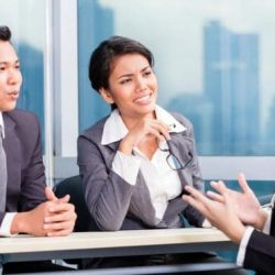 woman speaking with two job interviewers who are seated behind a desk