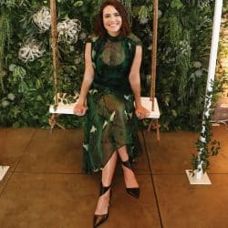 Mandy Moore poses outdoors sitting on a swing