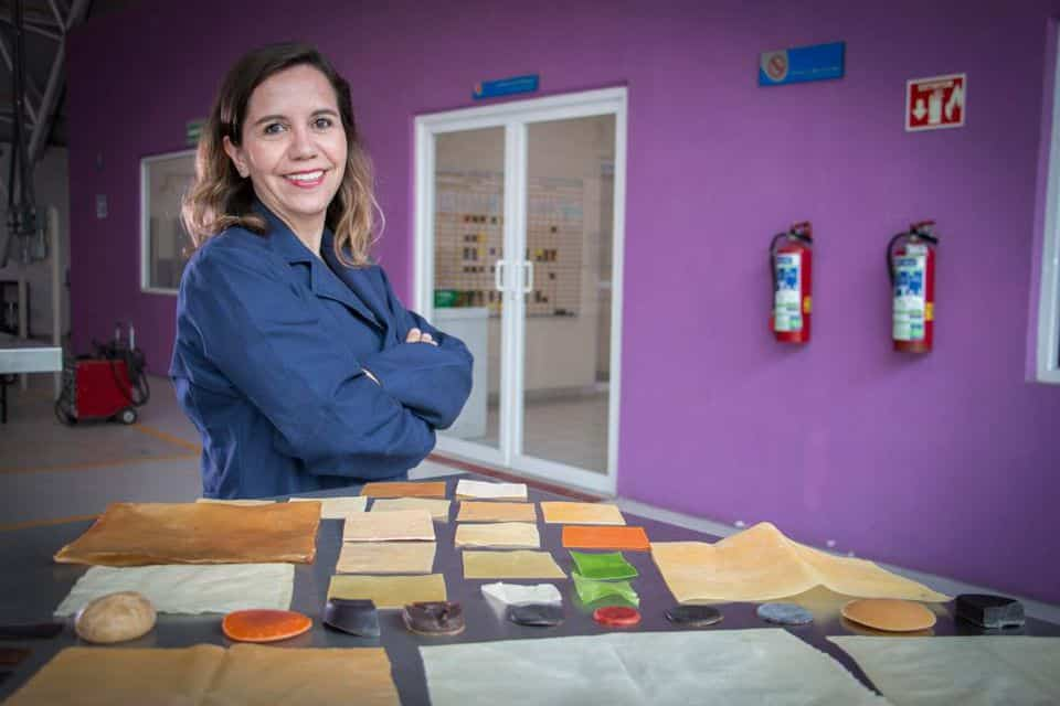Sandra Ortiz stands in kitchen behind table filled with vaiations of her new plastic