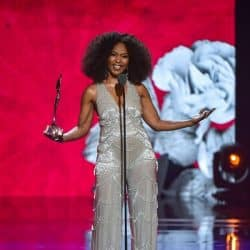 actress Angela Bassett speaks onstage wearing sequined outfit