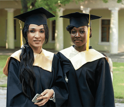 recent MBA graduates pose in cap and gown outside university