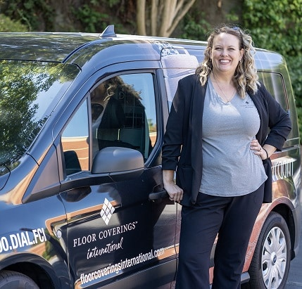 Krista Farley pictured standing in front of her Floor Coverings work vehicle