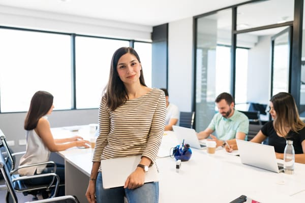 confident businesswoman with laptop at desk in office