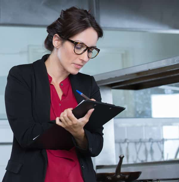 woman restaurant manager with clipboard inspecting kitchen