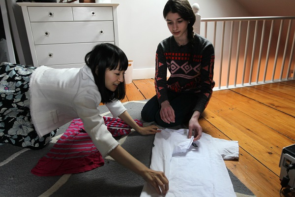 Marie Kondo gives folding lesson to young woman while both seated on the floor