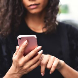 Closeup image of a woman holding, using and looking at smart phone with feeling happy
