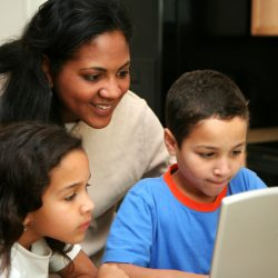 Mother and two children in the kitchen on the computer