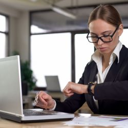 Busy woman looking at watch and concerned she is missing deadline