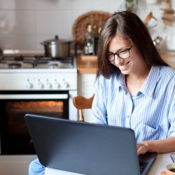 Young woman working from home office. in kitchen