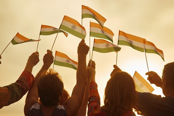 A group of people, mostly women, holding small Indian flags in the air.